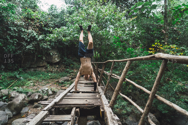 Unrecognizable man standing on hands on grungy wooden bridge in green forest.