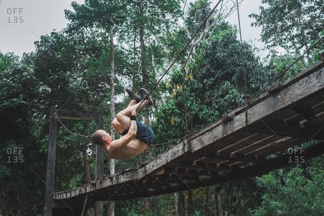Shirtless acrobatic man hanging on rope of grungy wooden bridge in the forest.