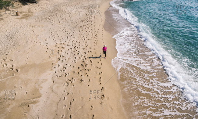 Photography aerial of woman doing running on a secluded beach on a sunny day.
