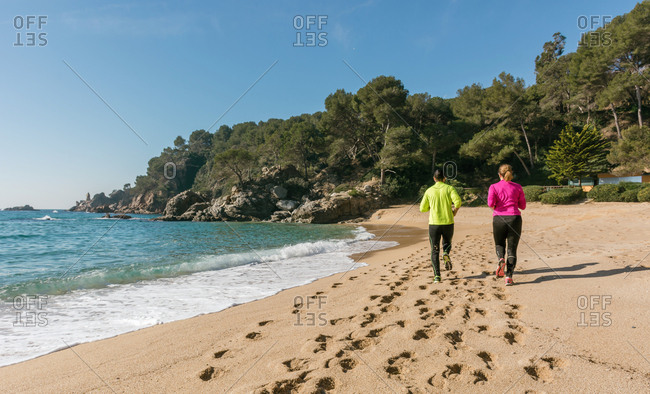 Couple running along a secluded beach on a spring day