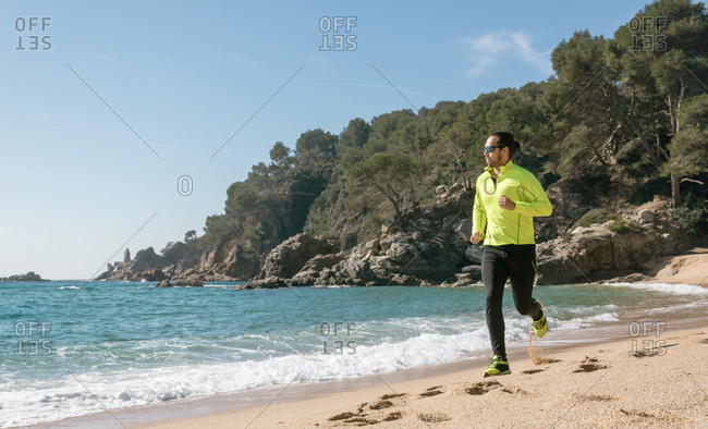 Latin male playing sport on a secluded beach on a sunny day of spring