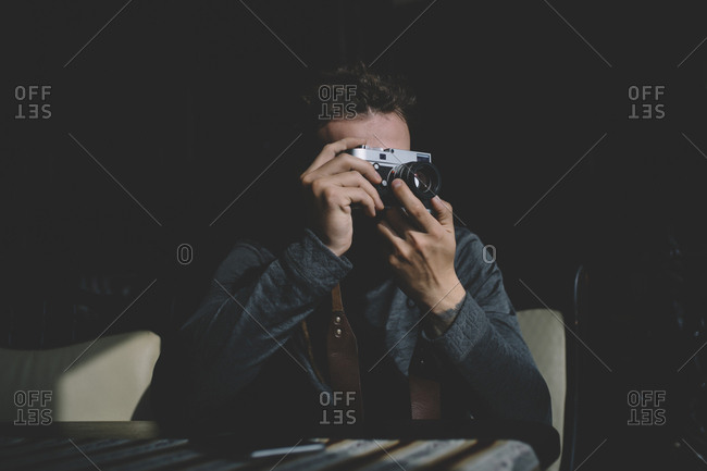 Unrecognizable photographer man sitting and aiming with photo camera.