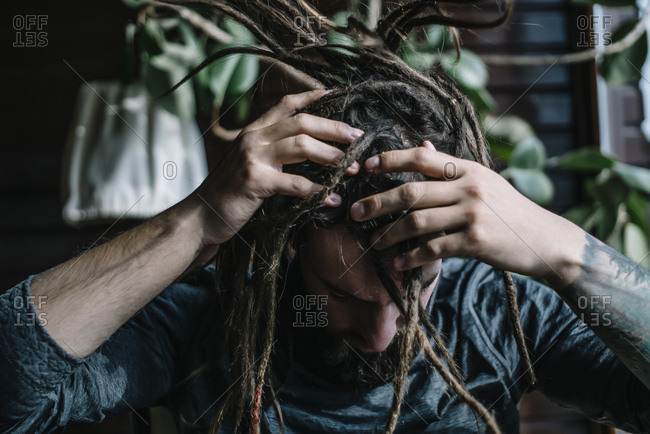 Unrecognizable informal man shaking head with dreadlocks hairstyle.