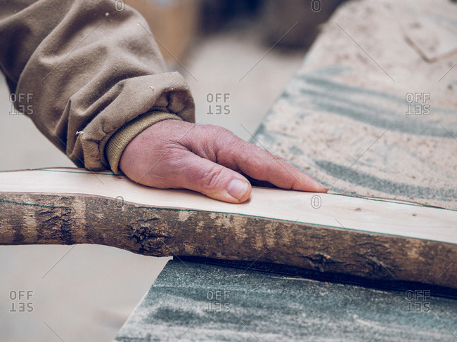 Crop hand of unrecognizable carpenter working with piece of wood on table in workshop.