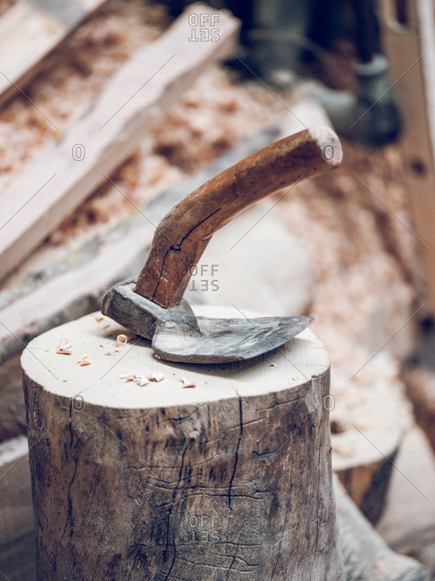 Artisan axe instrument on snag in the workshop.