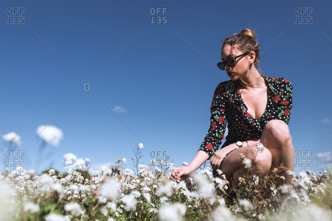 Attractive young woman in sunglasses standing on white field with flowers.