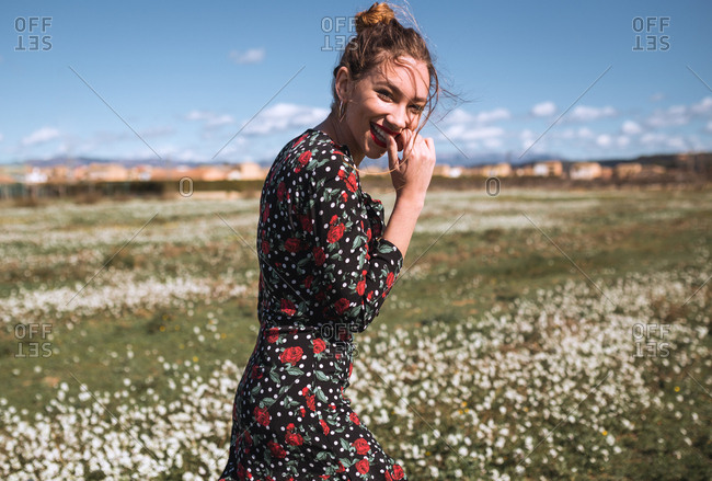 Young attractive woman standing on field with small flowers and looking at camera.