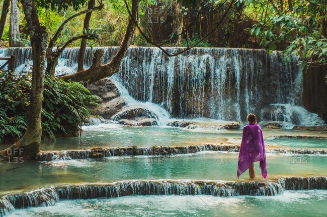 Tourist standing at waterfall
