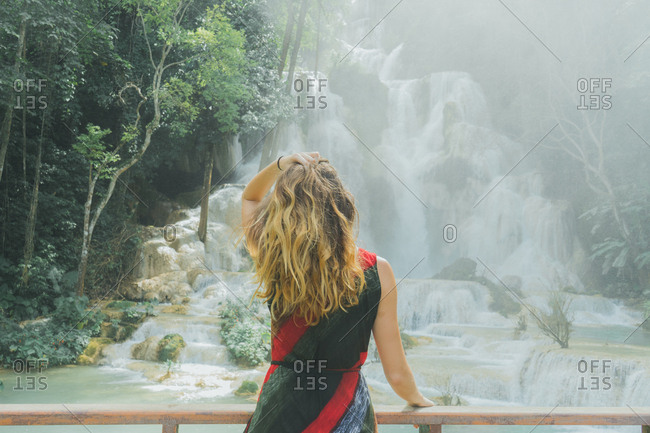 Back view of blonde woman holding hair and looking at cascade from the bridge.