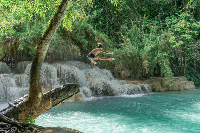 Unrecognizable man jumping high to turquoise water at the waterfall.