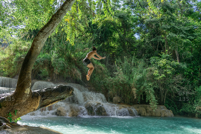 Man jumping to turquoise water