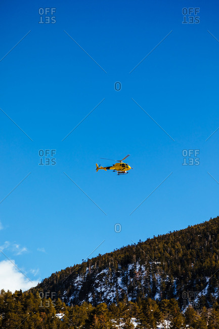 Rescue helicopter flying in a snowy landscape