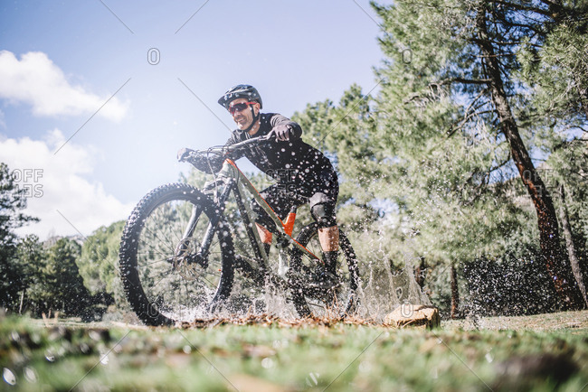Man cyclist splashes water with mountain bike.