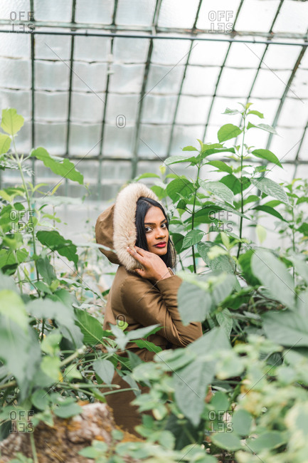 Indian Ethnic young woman in warm hood looking at camera in the hothouse.