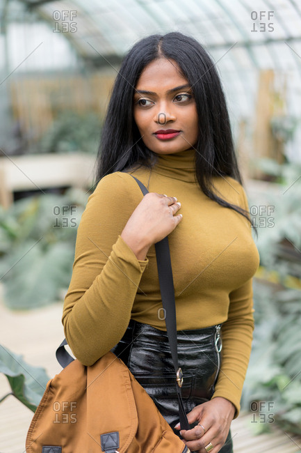 Pretty young stylish Indian ethnic woman with backpack standing in hothouse.