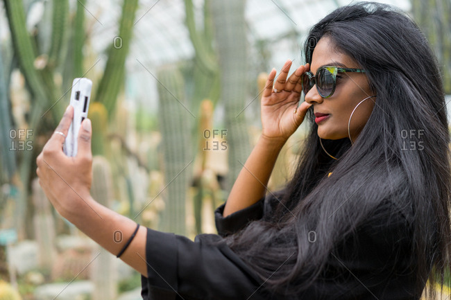 Pretty young ethnic woman taking selfie at the cactus in hothouse.