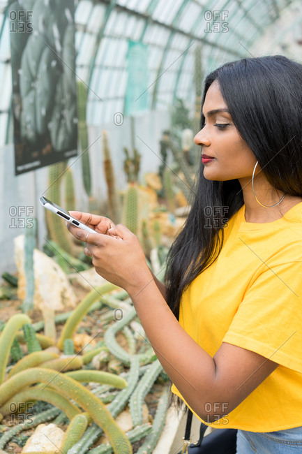 Pretty young ethnic woman with phone in hothouse.