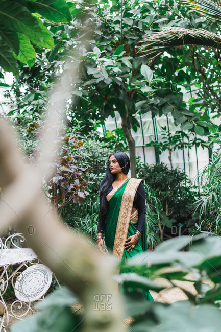 Ethnic young woman in traditional clothes standing at palm leaf in the garden.