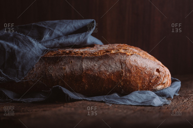 Rustic loaf of artisan bread on dark background
