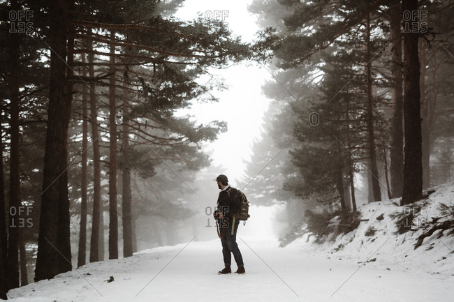Side view of tourist man standing in evergreen forest covered with snow.