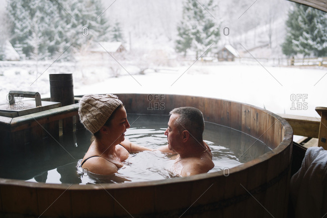 Sensual tattooed couple sitting in plunge tub in winter.