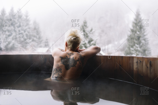 Back view of tattooed blonde woman swimming in plunge tub in winter nature.