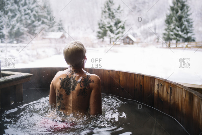 Back view of woman swimming in outside plunge tub in winter nature.