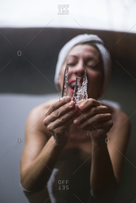 Cheerful woman in outside plunge tub with icicle in winter day.