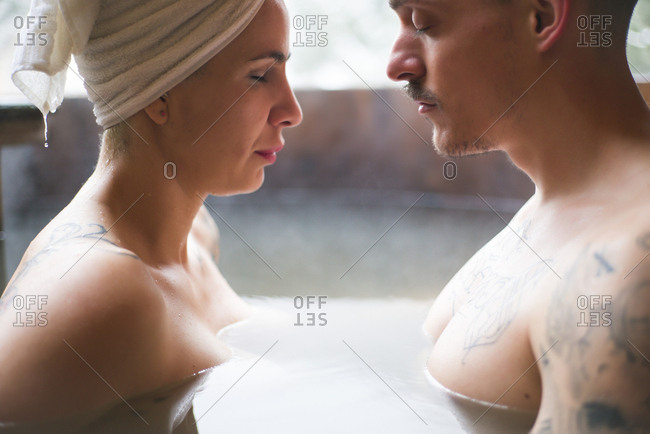 Side view of sensual tattooed couple sitting in plunge tub in winter.