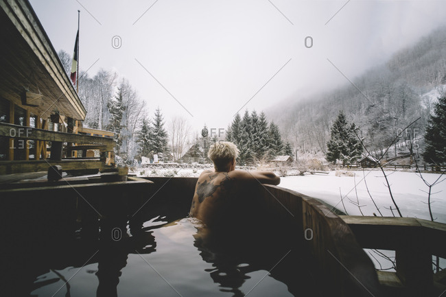 Back view of tattooed woman swimming in plunge tub and looking at winter nature.