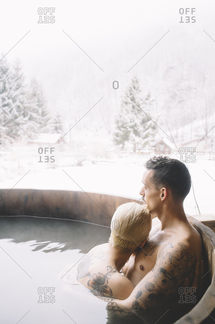 Couple sitting in plunge tub in winter