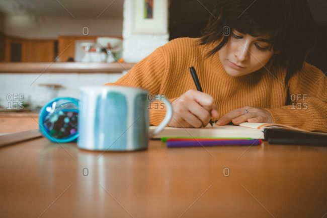 Woman drawing a sketch in a book at home