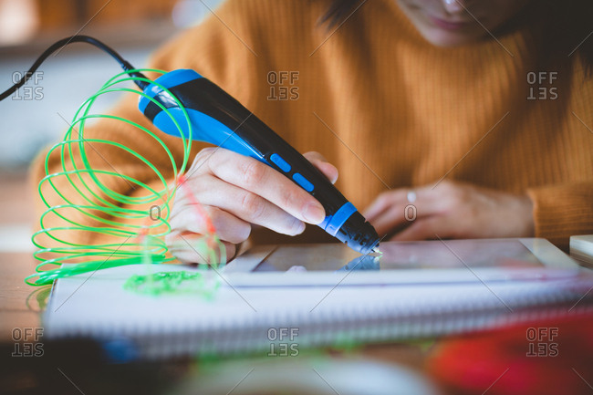 Woman using electric pen on digital tablet