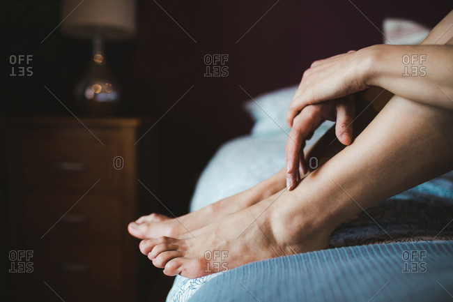 Woman relaxing on a bed in bedroom at home