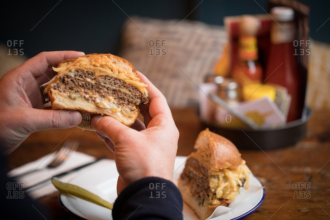 Close-up of man eating burger in restaurant