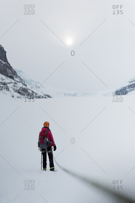 Rear view of female hiker standing with backpack on a now covered mountain during winter