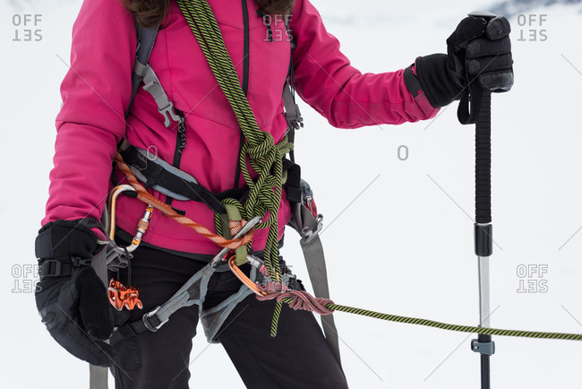 Midsection of female hiker standing with harness and rope in snowy region