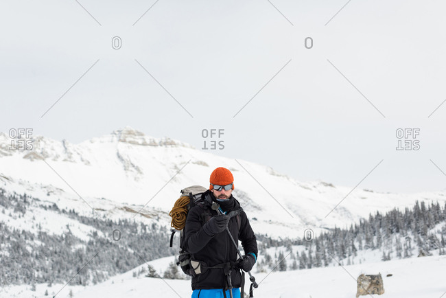 Male hiker holding ski pole on a now covered mountain during winter