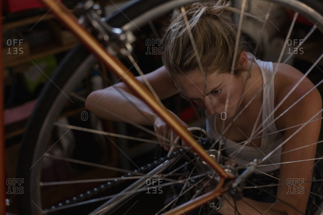 Young female mechanic fixing bicycle in workshop