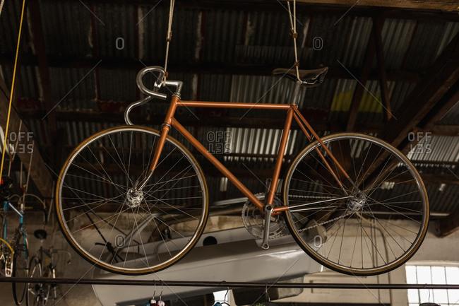 Racing bicycle hanging in workshop