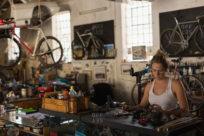 Female mechanic examining bicycle parts in workshop