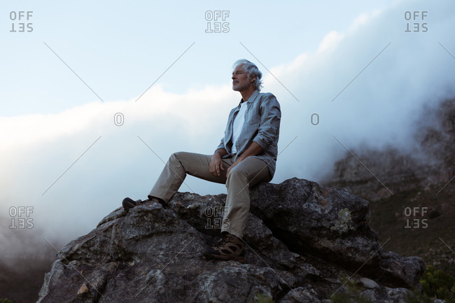 Senior hiker sitting on a rock in countryside