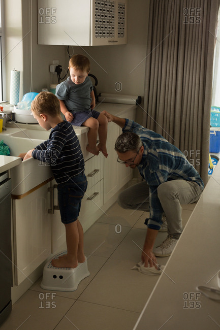 Father with his son cleaning kitchen room at home