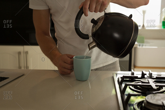 Mid section of man pouring hot water into mug at home