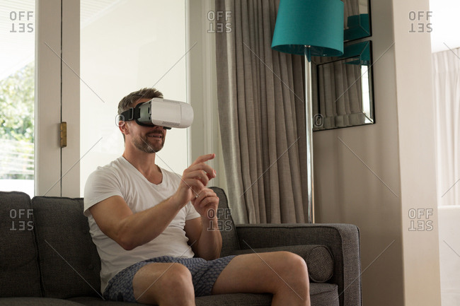 Man using virtual reality headset in living room at home