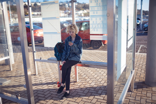 Woman using mobile phone at bus stop on a sunny day
