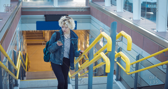 Young woman using mobile phone while moving upstairs