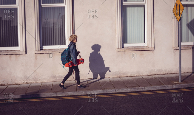 Woman walking with backpack and skateboard on a footpath in the city