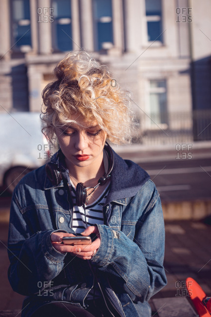 Young woman using mobile phone in city street
