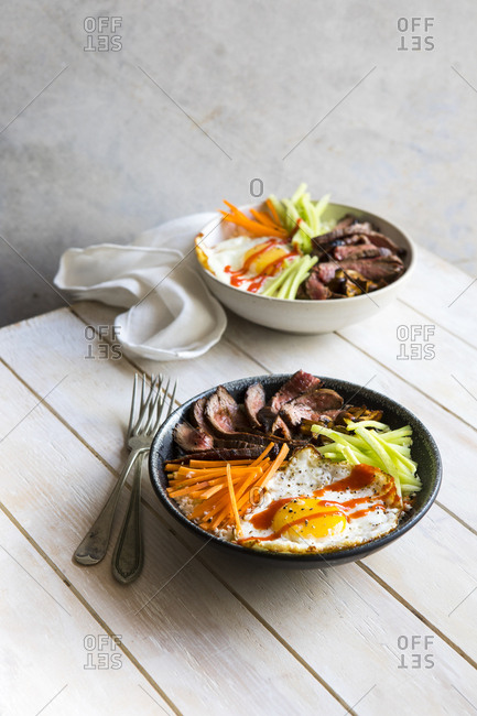 Bowl with beef, egg and rice on a white table